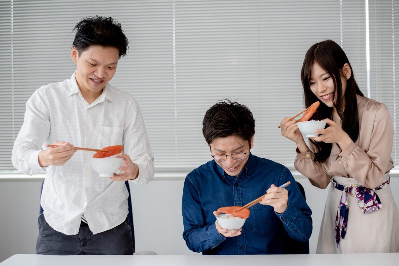 三人笑顔で明太子を食べる写真