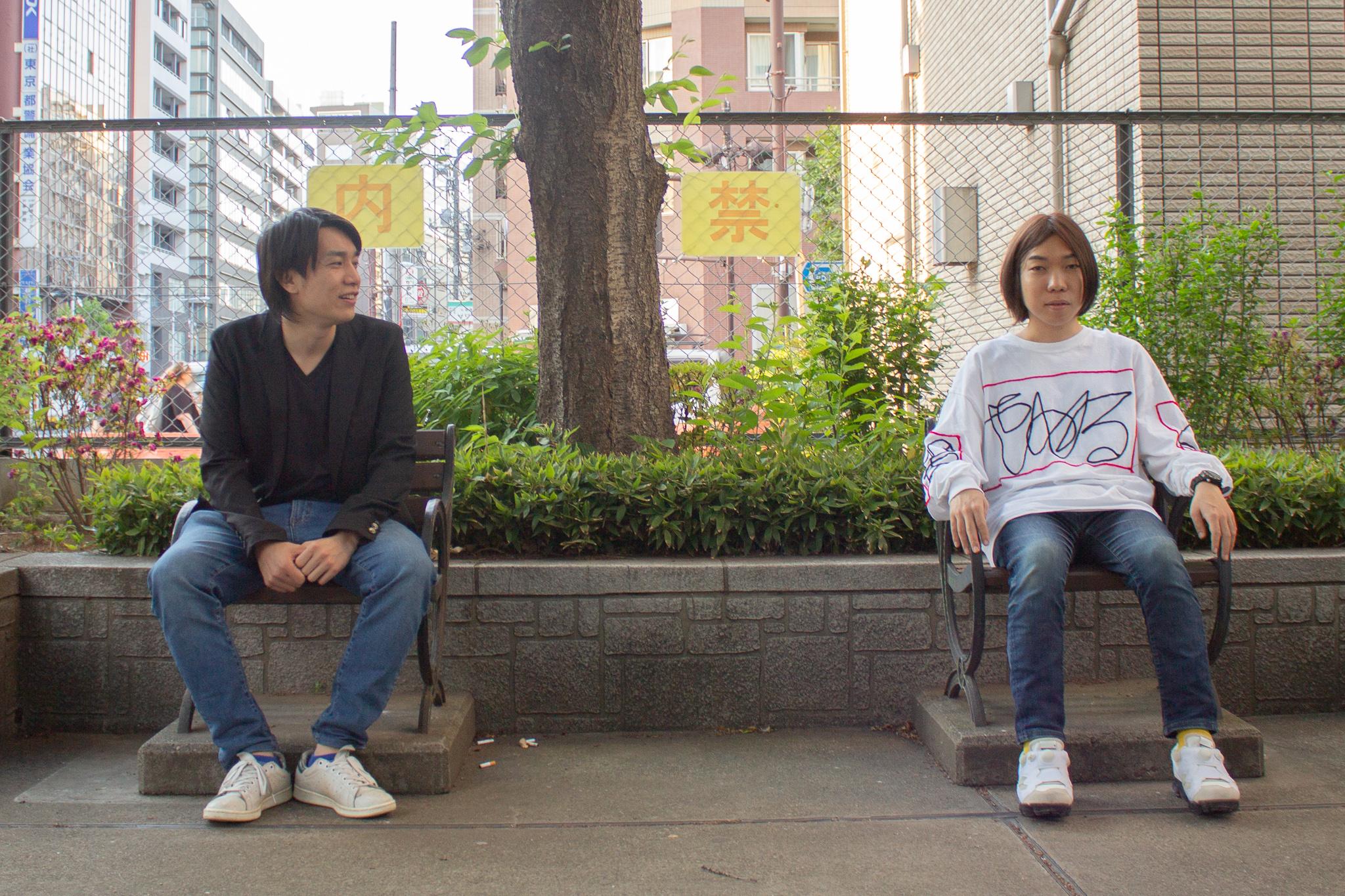 帝王的な感じで公園のベンチに座る菊池さん