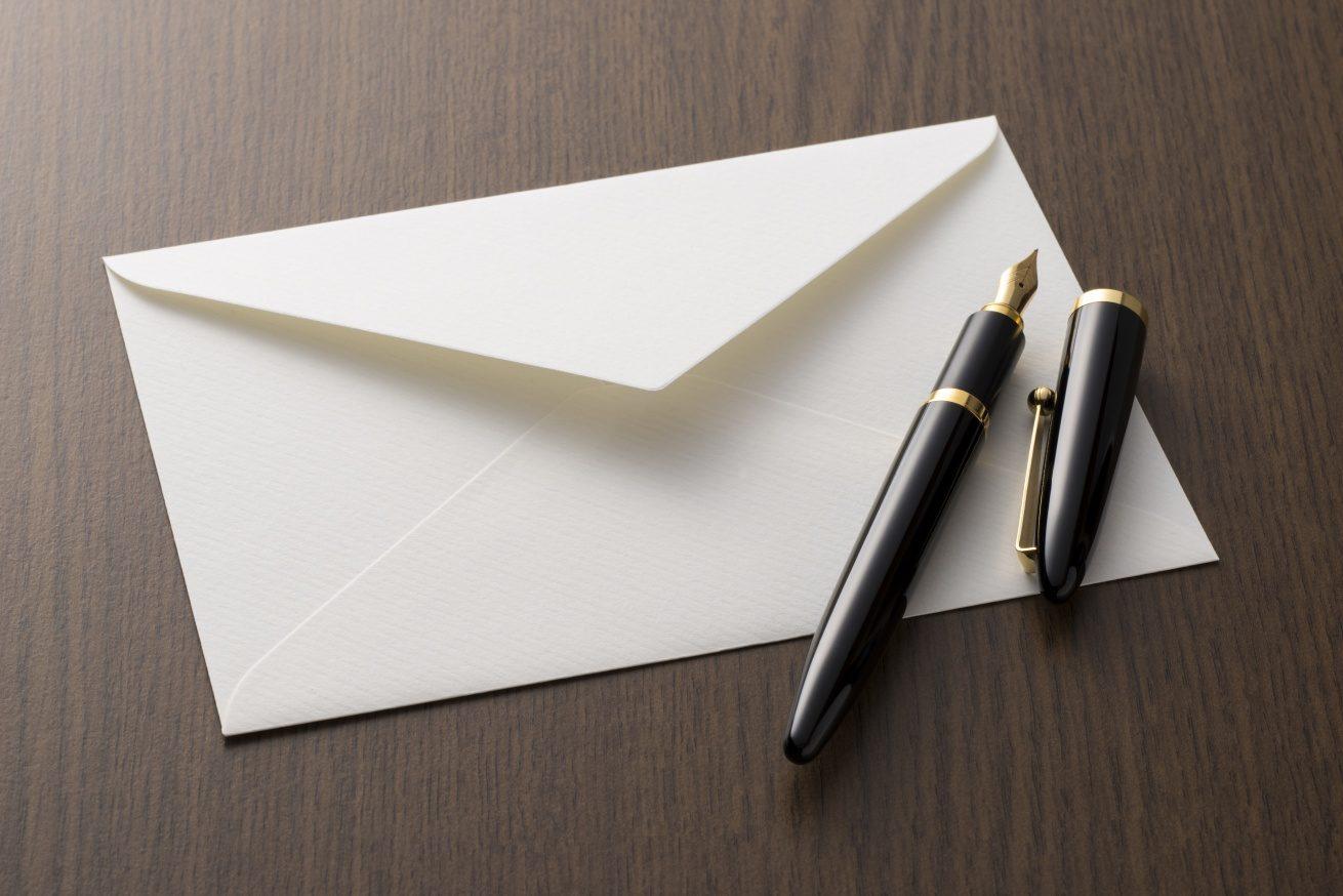封筒と万年筆の写真