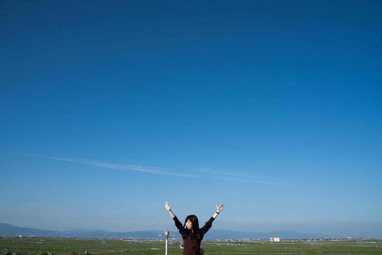 空港の屋上で両手を上げるまこりーぬ