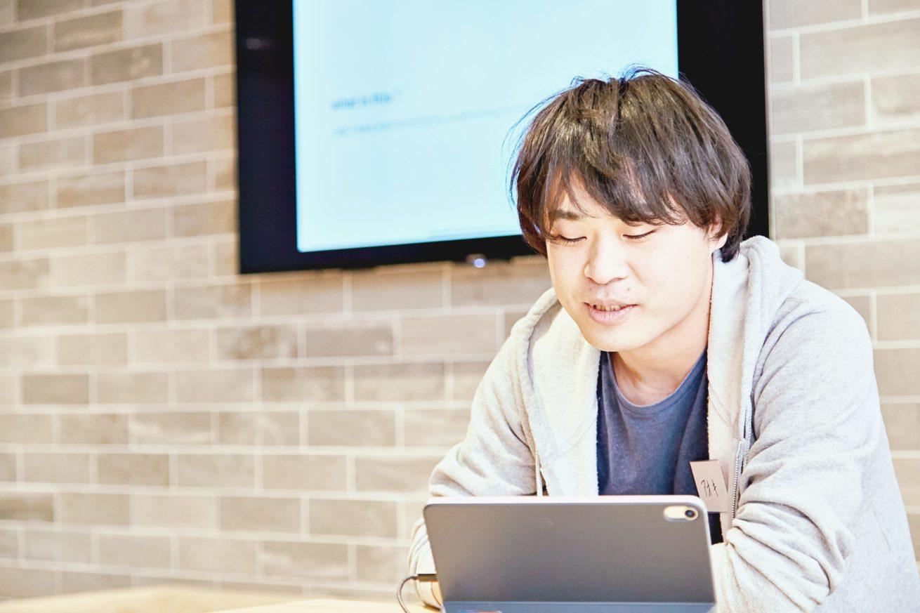iPadの画面を見ながら話す青木さん