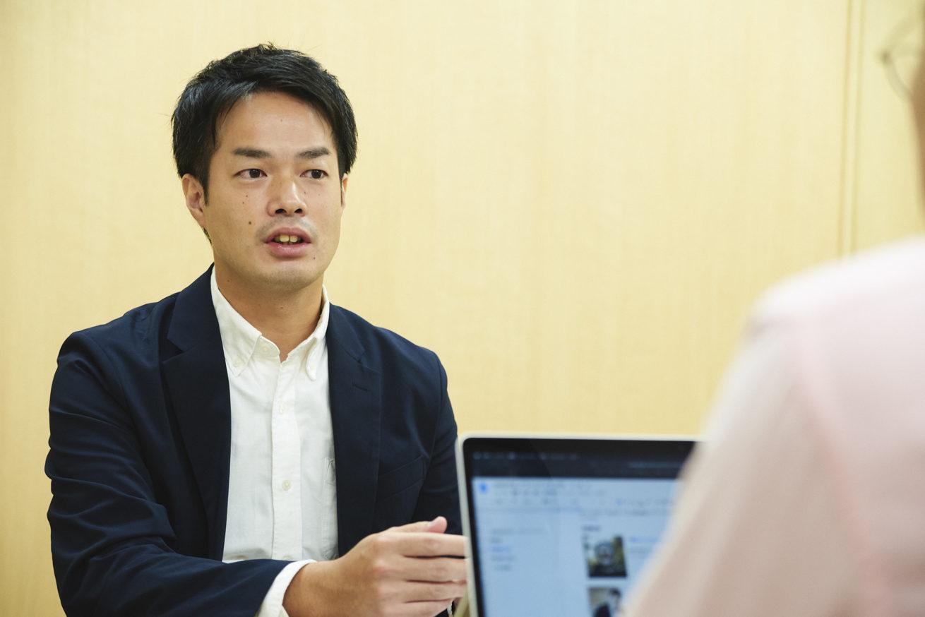 観音越しの村野さんが話をしている写真