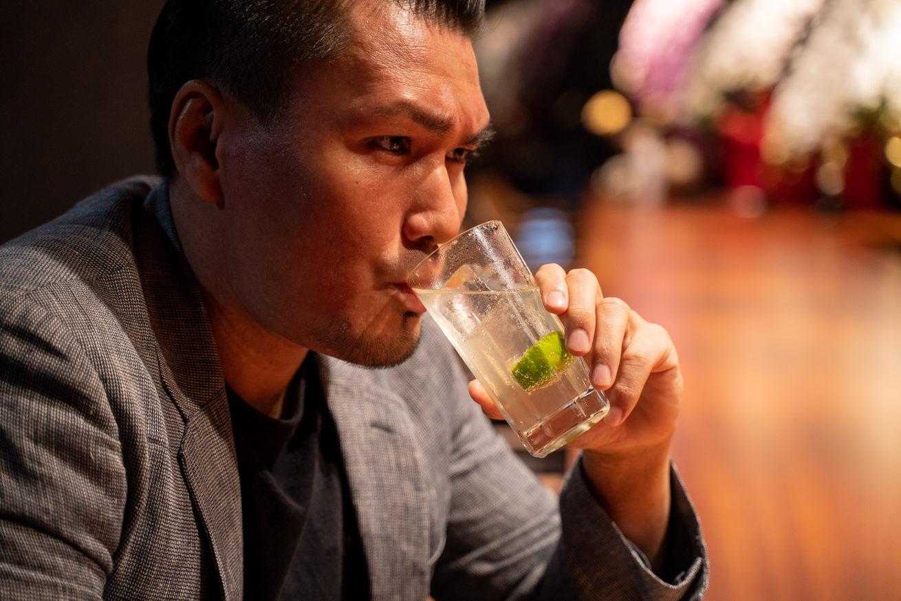 飲みながら渋い表情をするジョニー