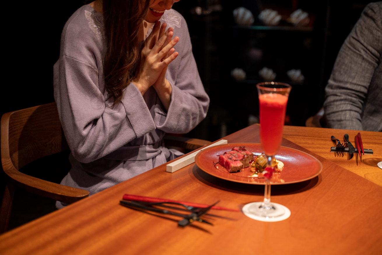 料理とドリンクを見て喜んでいる花子