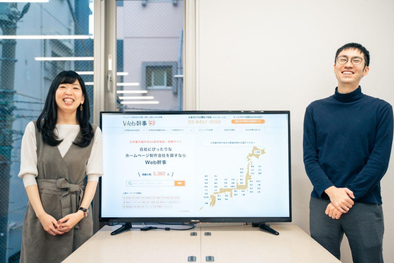 Web幹事のサイトが表示された大画面の左右に並ぶ2人