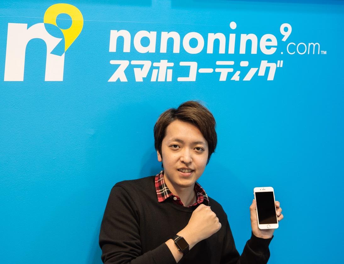 「ナノナイン.com」のロゴ前でスマホを持って正面を向くバンビ