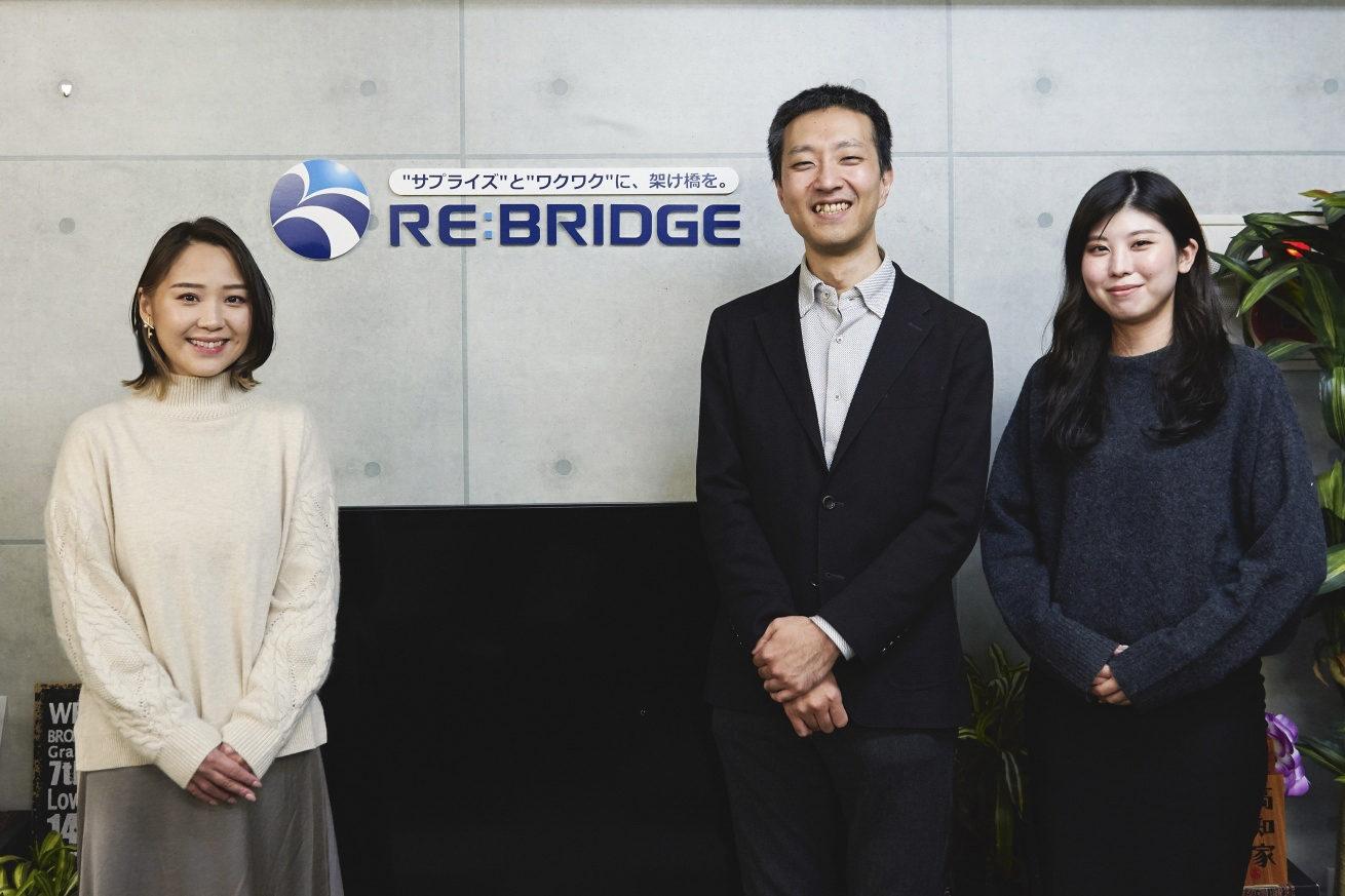 会社のロゴ前に笑顔で3人並んでいるカット