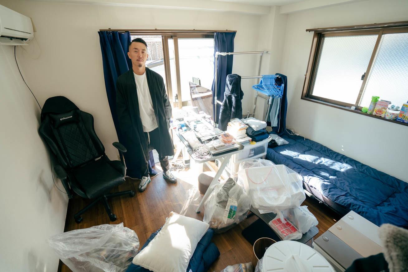 散らかった1Kの一室で土足で佇むLIG社長の吉原ゴウ