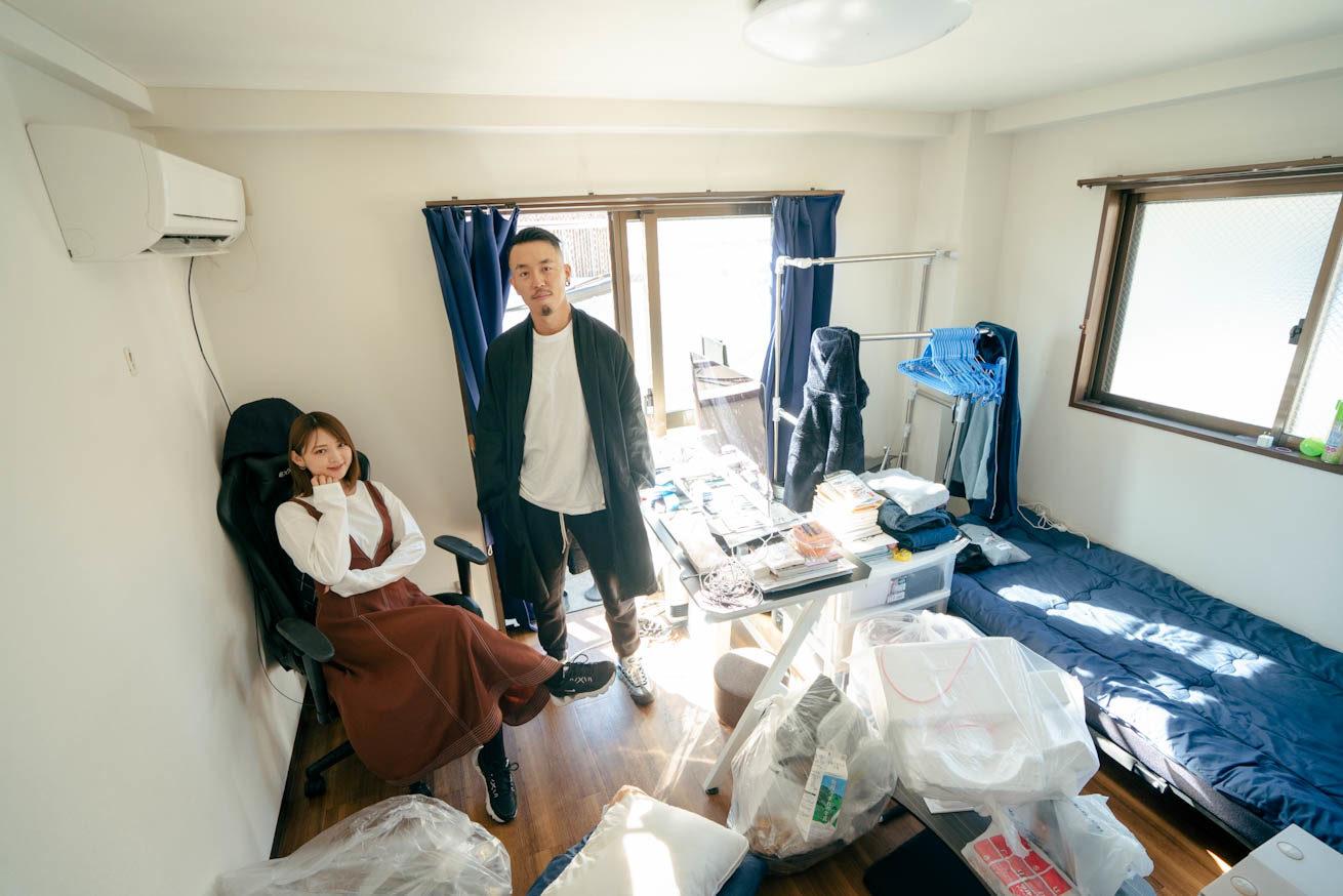 散らかった部屋で土足で佇むLIG社長の吉原ゴウとその横で椅子に座る鈴木さん