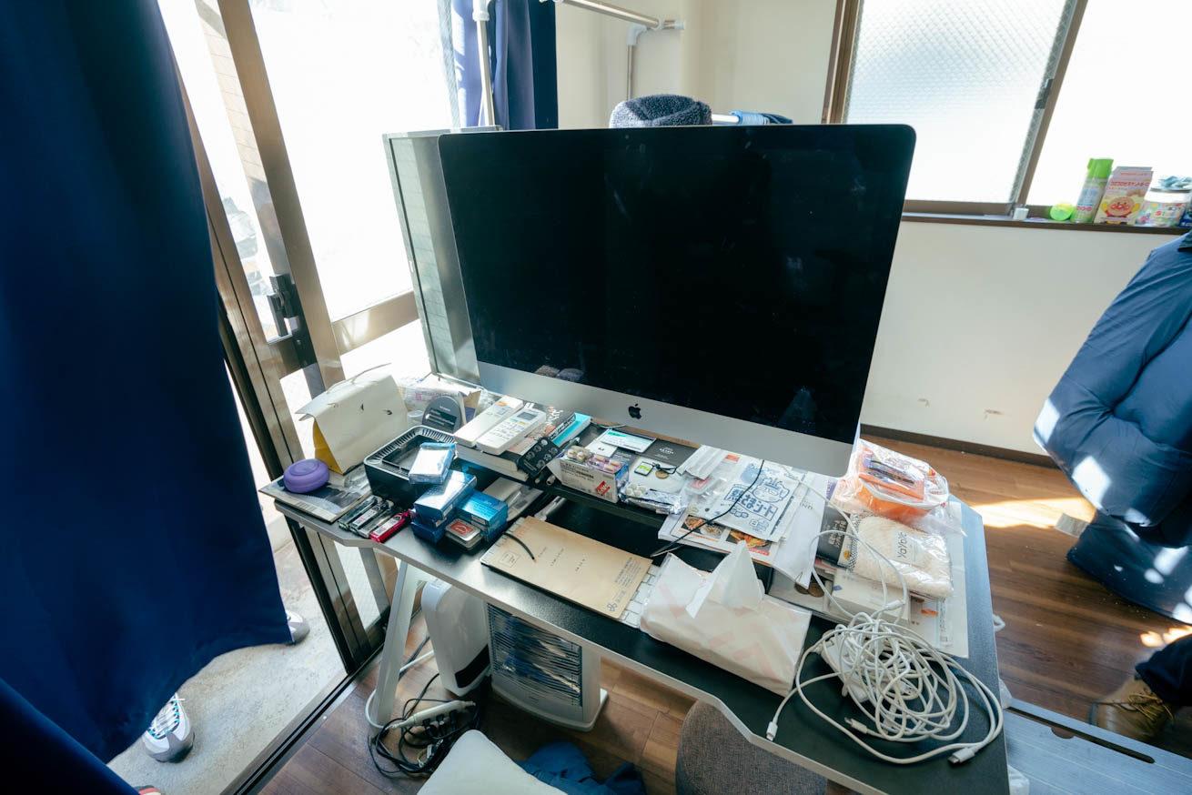 机の上にMacのデスクトップと散らかった小物