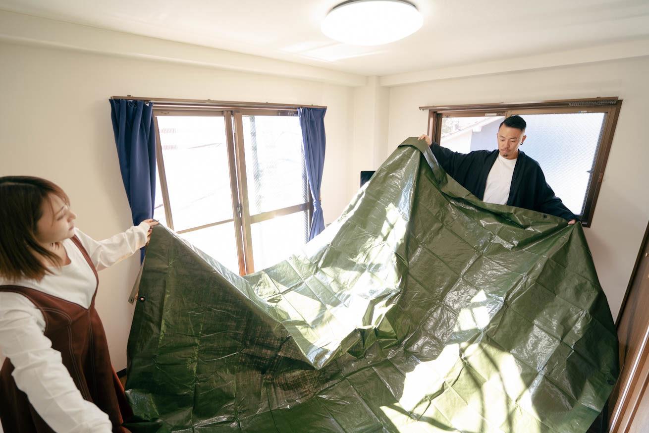 2人でグリーンの養生シートを床に敷いているシーン