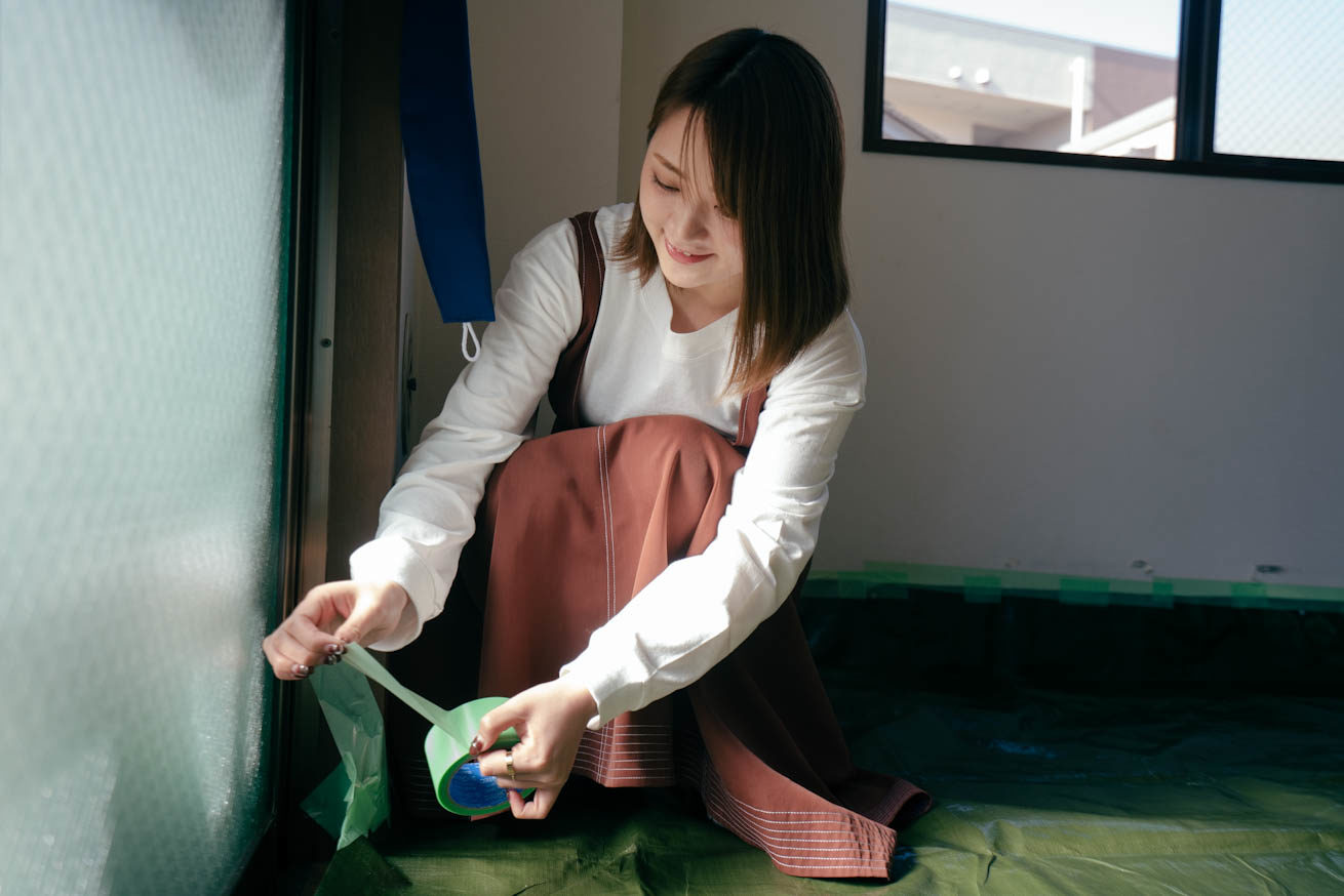 笑顔で養生テープを持っている鈴木さん