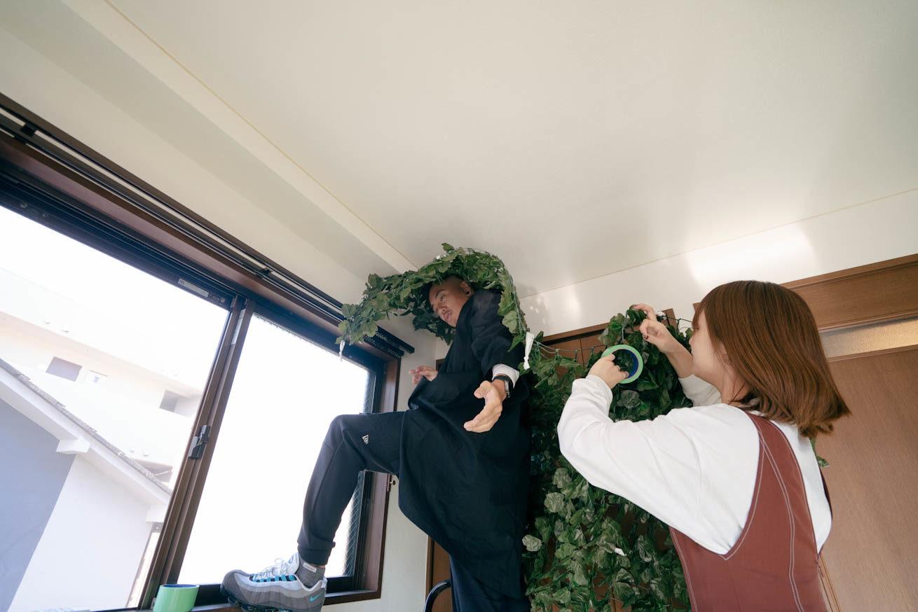 2人で協力して草を天井に貼り付けている様子