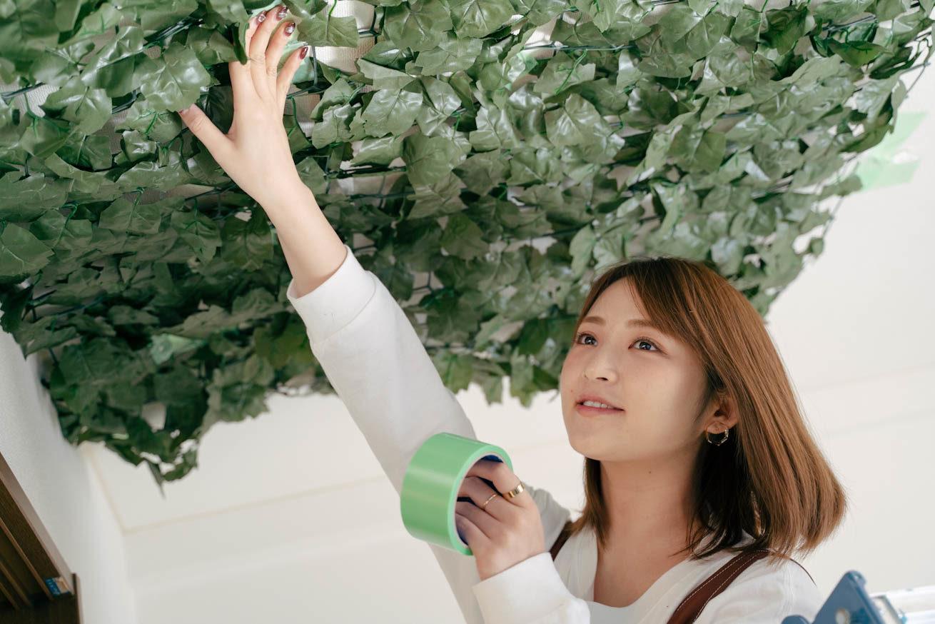 グリーンの養生テープを持って天井に貼る鈴木さん