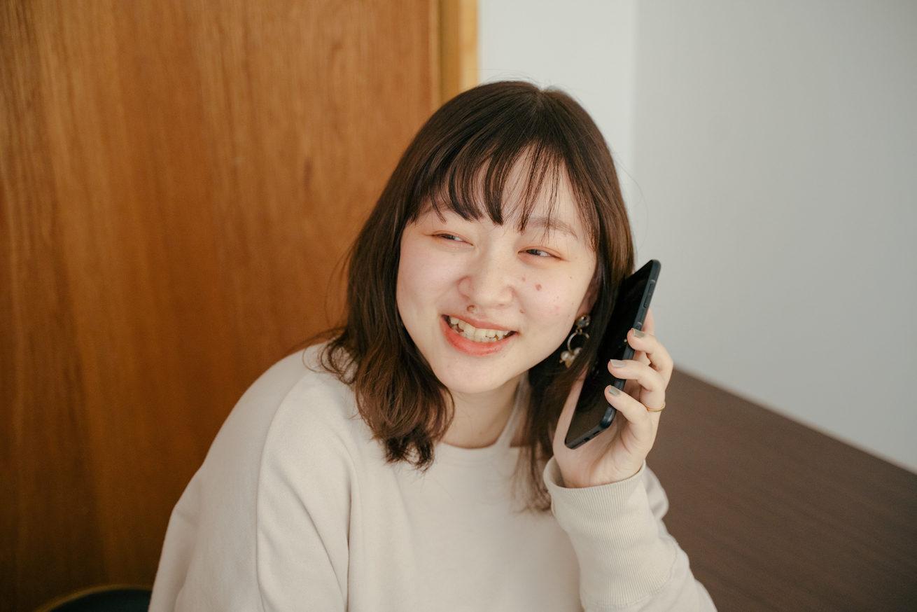 笑顔でスマホから電話をする人