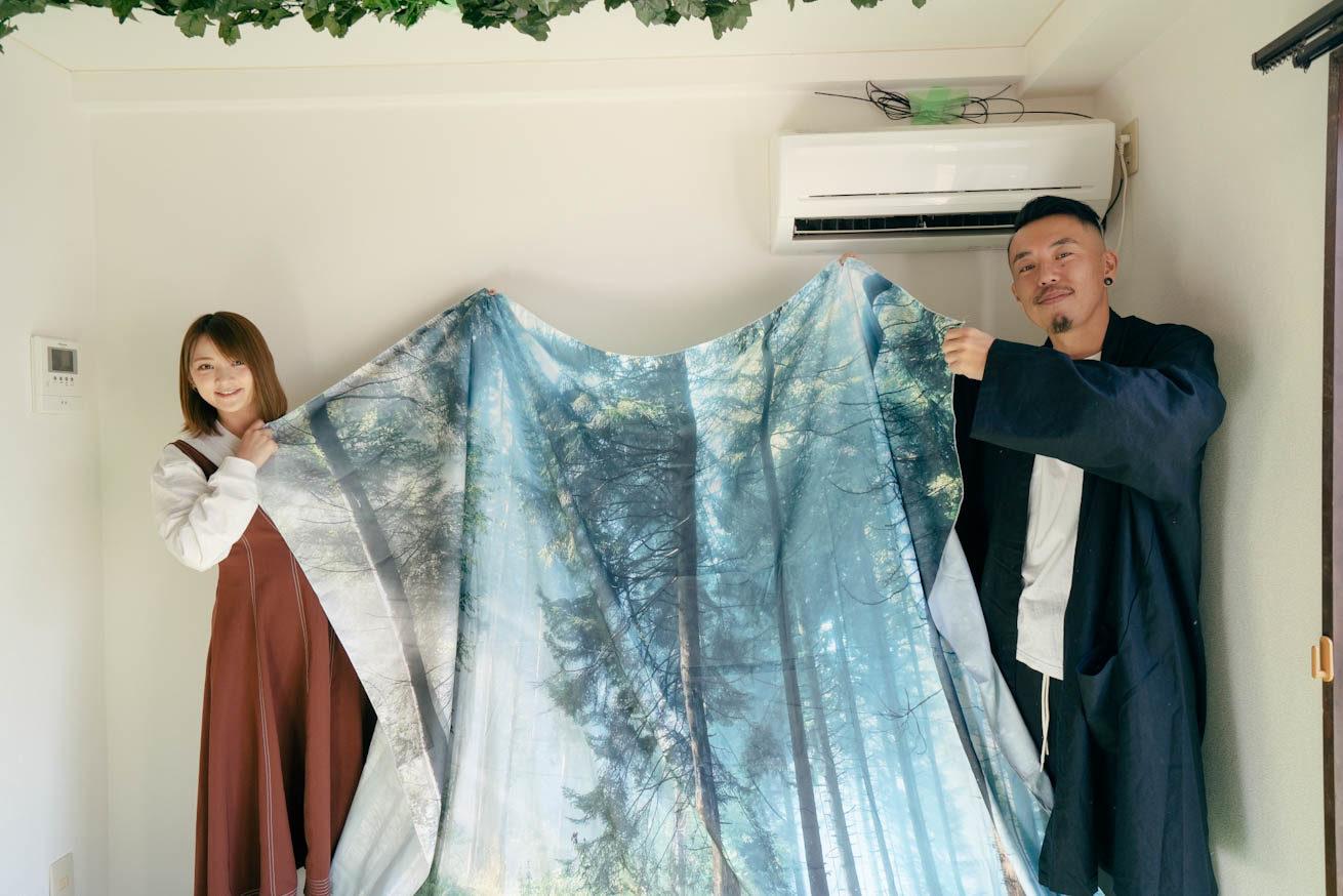 森が印刷された布の両端を2人で持っている