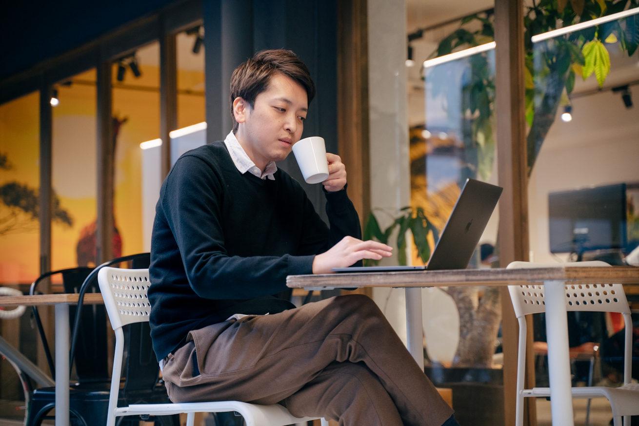 片手にコーヒーカップを持ちながらパソコンで仕事をするフリーランサー