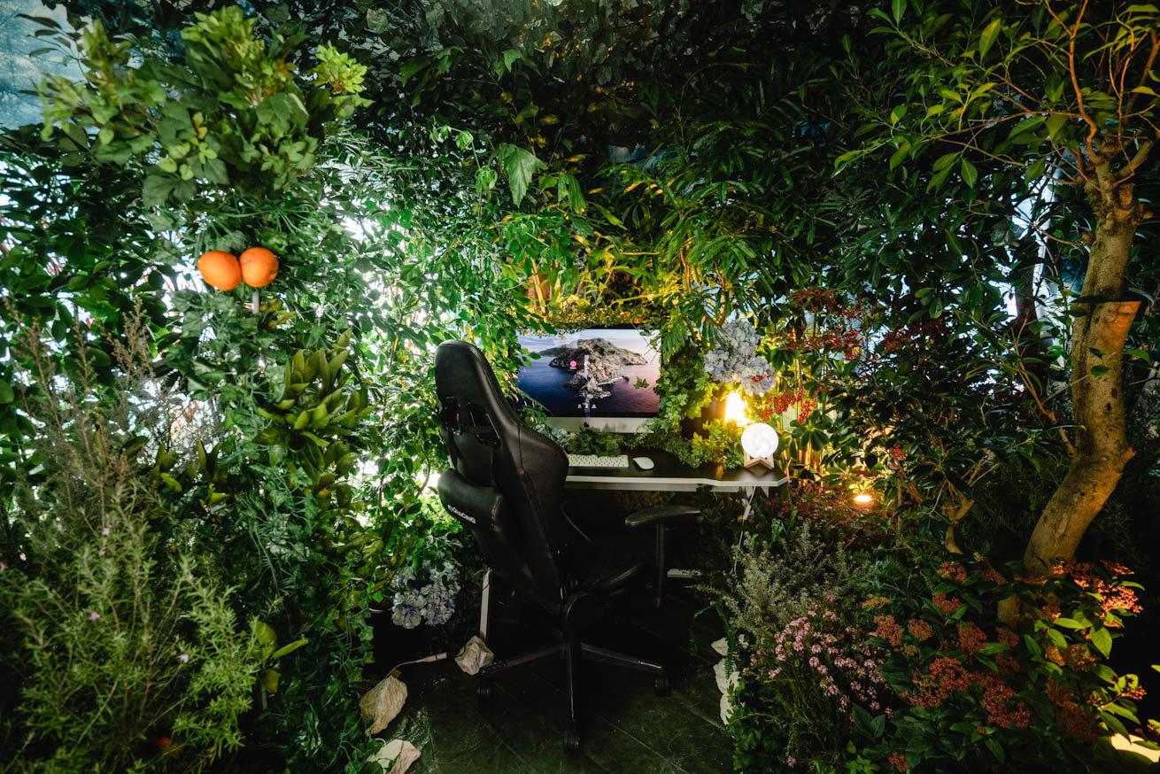 森の中にデスクとチェアーとPCが置いてある光景