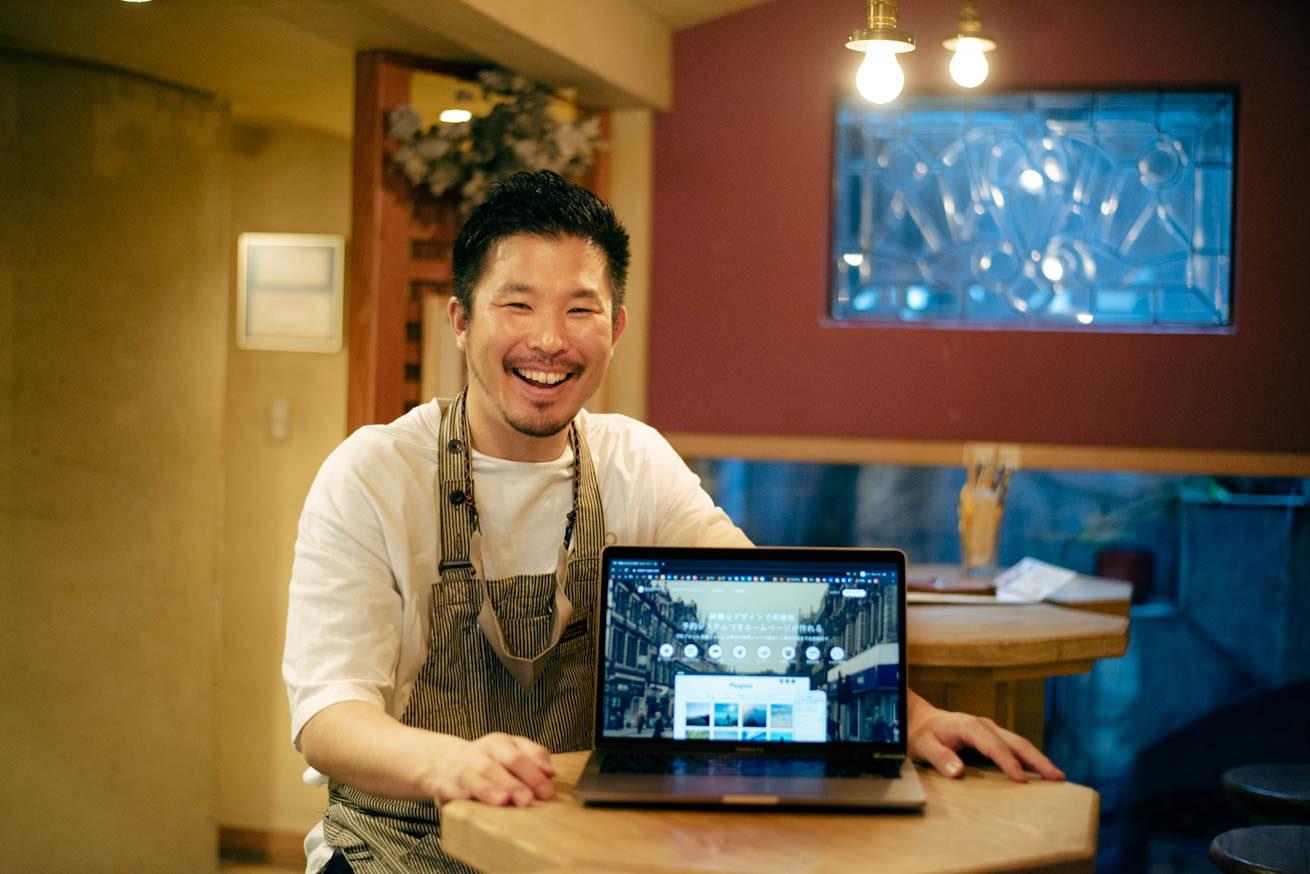 PCの画面にうつったSELECTTYPEのTOPページを笑顔で見せている堀田さん