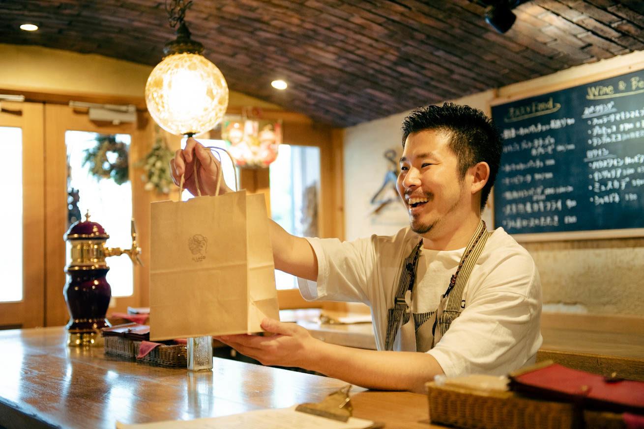 笑顔で品物を渡す堀田さん