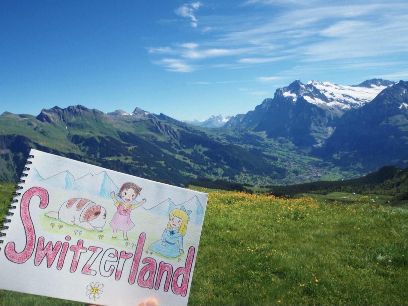 スイスを訪れたときの一枚。アルプスの自然をバックにスケッチブックに描かれたイラストを写している